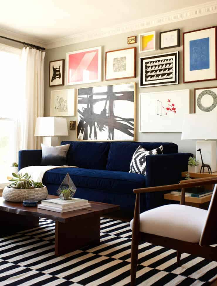 gallery wall above navy sofa