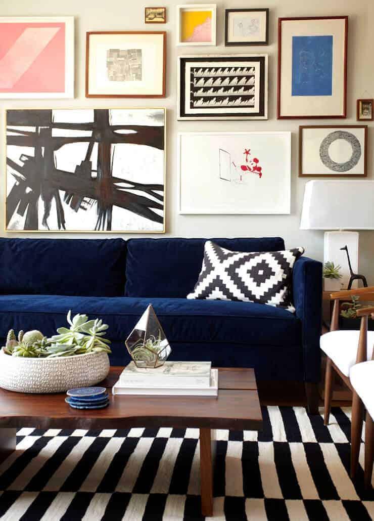 gallery wall above navy sofa